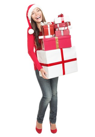 christmas gift: Christmas woman holding gifts wearing Santa hat. Standing in full body isolated on white background. Smiling woman portrait of a beautiful mixed Asian  Caucasian model.