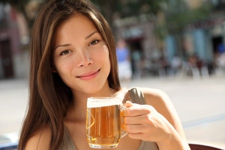 Beer woman enjoying a fresh draft beer outside on sidewalk cafe. Beaufiful Caucasian  Asian model. Stok Fotoğraf