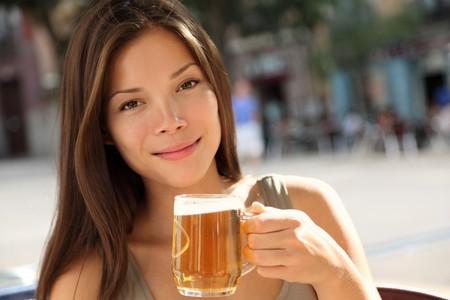 Bier vrouw genieten van een verse ontwerp bier buiten op de stoep cafe. Beaufiful Kaukasische  Aziatische model. Stockfoto