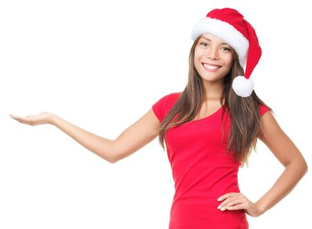 copyspace: Christmas woman showing copyspace for product with open palm. Young smiling woman with red santa hat. Image of beautiful young Caucasian  Asian model isolated on perfect white background. Stock Photo