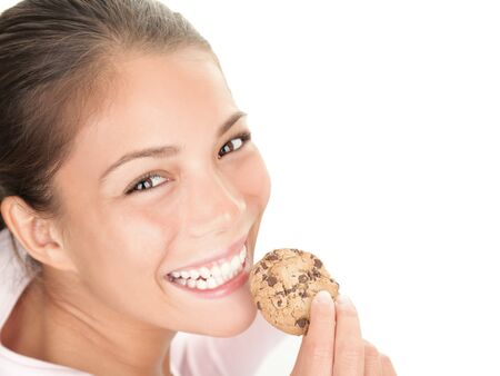 chocolate chip cookies: Cookie woman eating chocolate chip cookies on white background. Cute young mixed race chinese  caucasian woman smiling. Stock Photo
