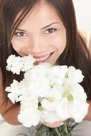 Girl holding flowers. Cute young asian / caucasian woman smiling showing white flowers. Stock Photo - 7990028