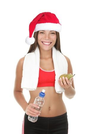 Gezond fitness vrouw in Santa hat geïsoleerd op een witte achtergrond. Mooie fit gemengd Aziatische Chinees  Kaukasische vrouwelijke model houden een peer en een fles water dragen van fitness outfit en rode kerstmuts. Stockfoto