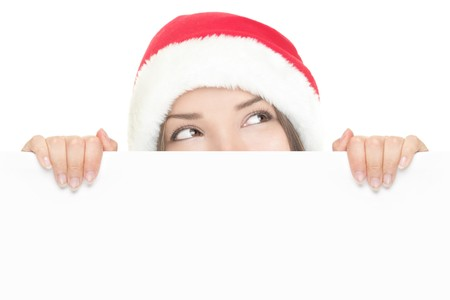 Girl in Santa peeking over paper sign board looking up. Cute funny photo closeup of christmas woman with copyspace. Isolated on white background. photo