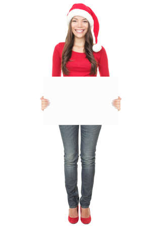 Christmas woman holding empty paper sign standing in Santa hat. Mixed Asian  Caucasian young woman model isolated in full length on white background.  photo