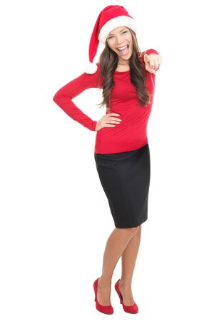 Pointing Santa girl happy for christmas and excited pointing at camera standing in full length isolated on white background. Young smiling asian  caucasian woman. photo