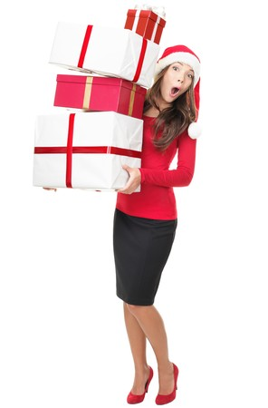 Christmas shopping. Santa woman standing holding gifts with funny expression isolated on white background. Young mixed race Asian Chinese  white Caucasian model.  Stock Photo