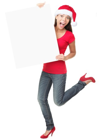 Christmas sign excited woman looking happy and surprised. Funny asian caucasian female model standing full body isolated on white background.  photo