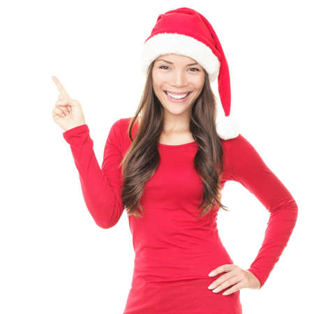 Beautiful smiling christmas santa woman pointing up showing copyspace. Isolated on white background. photo