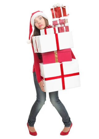holiday spending: Christmas shopping gifts. Stressed woman with funny expression holding many gift boxes.
