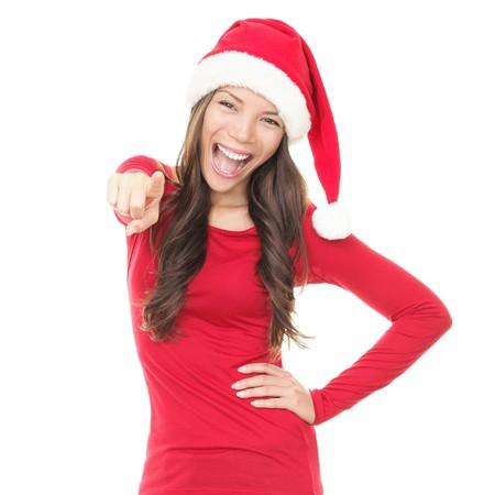 ragazza che indica: Donna in santa cappello eccitato per Natale. Sorpresa bella felice ragazza asiatica che punta a telecamera isolato su sfondo bianco.