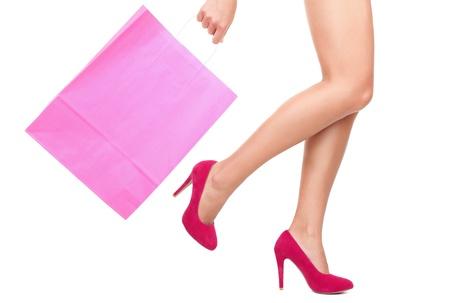 tacones rojos: Piernas de la bolsa de compras de mostrar de dama con copyspace de compras. Aislados sobre fondo blanco.