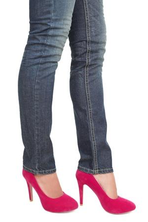 Vrouw in hete roze rood hoge hakken en jeans. close-up van half onderlichaam geïsoleerd op een witte achtergrond. Stockfoto