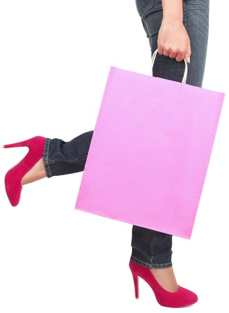 woman holding bag: Legs of shopping lady showing shopping bag with copyspace. Isolated on white background. Stock Photo