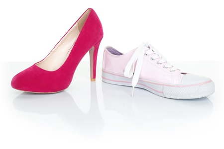 high contrast: High heels shoes vs casual sports shoes  sneakers. On white background. Stock Photo