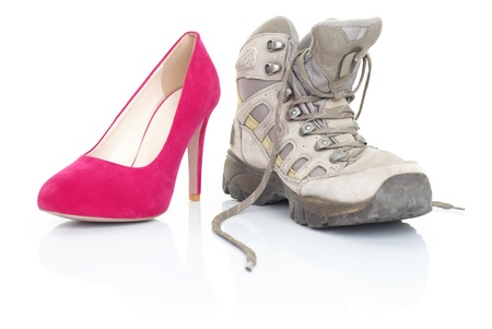 Opposites. Woman shoes on white.  One pink red high heels and one hiking shoe.