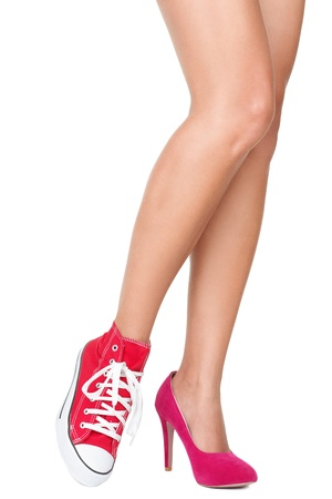 sneakers: Women shoes. Red high heels and sports shoes  sneakers. Closeup of woman legs and feet wearing two different shoes. Isolated on white background.
