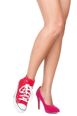 tacones rojos: Zapatos de mujer. Red de alta escore y zapatos de deportes  zapatillas de deporte. Detalle de las piernas de la mujer y los pies llevando dos zapatos diferentes. Aislados sobre fondo blanco.