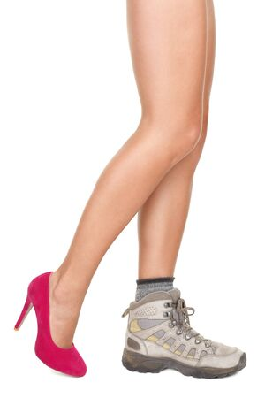 hiking boot: Shoe choice concept image. Sexy woman legs wearing one high heels shoe and one hiking shoe. Stock Photo