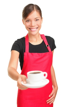 Coffee serving waitress. Young asian barista woman smiling showing cup of coffee. Isolated on white background. Focus on waitress.
