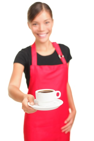 Waitress serving coffee. Barista cafe shop woman smiling showing cup of coffee. Isolated on white background. Focus on coffee. photo