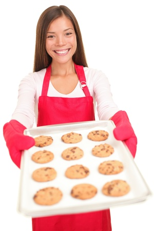 Baking woman showing tray of cookies fresh from oven. Beautiful young smiling woman isolated on white background. photo