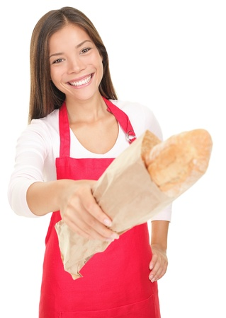 store clerk: Smiling woman sales clerk giving baguette bread to customer (camera). Isolated on white background.