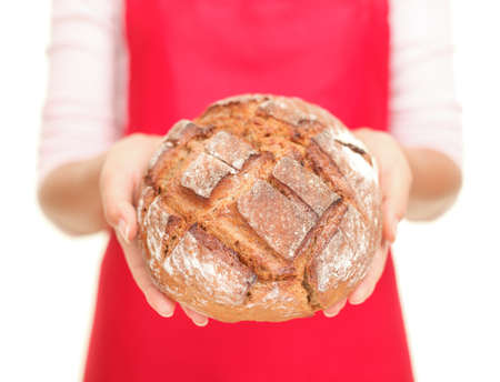 Bread. Closeup of woman showing fresh baked healthy whole grain bread. White background. photo