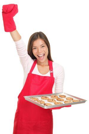 jasschort: Bak vrouw opgewonden met arm opgegroeid in succes houden een lade van cookies. Jonge lachende Aziatisch  blanke vrouw geïsoleerd op een witte achtergrond. Stockfoto