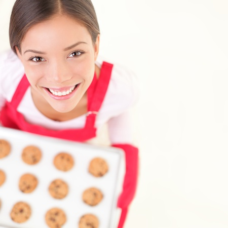 woman baking: Baking woman smiling holding tray of cookies. Copy space for text. Stock Photo