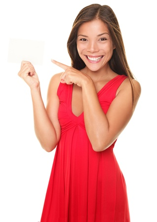 Woman pointing at sign. Young beautiful sexy woman showing copy space on empty blank sign or gift card. Portrait of smiling Asian Chinese / white Caucasian isolated on white background.