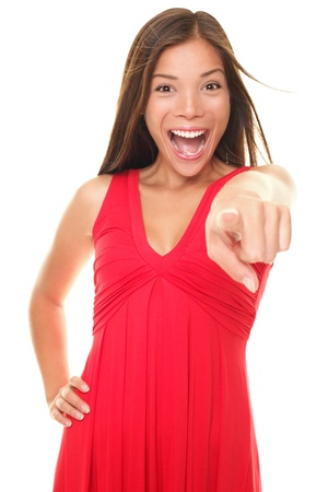 Woman pointing energetic at camera excited and happy. Isolated portrait of young cheering Asian  Caucasian female model in red dress on white background. photo