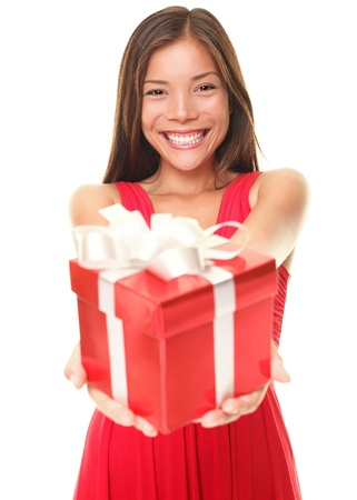 Gift woman in red smiling showing present. Beautiful Asian  Caucasian girl isolated on white background. Shallow depth of field, focus on woman
