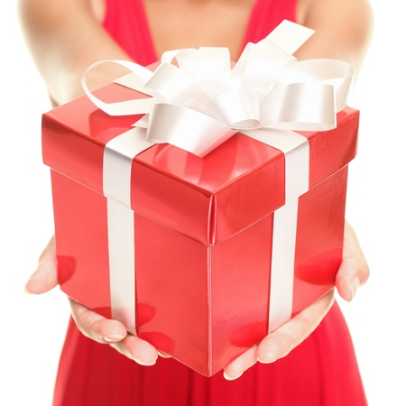 Gift woman showing beautiful red gift box - closeup of present on white background. photo