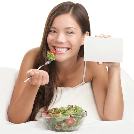 ni�a comiendo: Ensalada copyspace. Mujer comiendo ensalada mostrando signo en blanco con espacio de copia. Saludable comer concepto con joven asi�tica sonrientes mirando la c�mara. Espacio para texto.