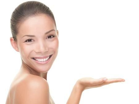 productos naturales: Cuidado de la belleza. Retrato de belleza de Palma de mano abierta vac�a de hermosa mujer bell�sima mostrando. Asia  cauc�sico j�venes mujer modelo mixto aislado sobre fondo blanco. Foto de archivo