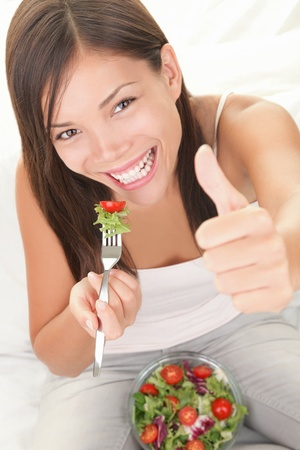 Salad. Eating healthy concept showing happy woman eating salad giving thumbs up. photo