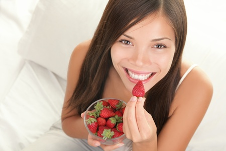 eating: Portrait of woman eating strawberries. Healthy happy smiling woman eating strawberry inside in bed holding a bowl of strawberries. Gorgeous smile on mixed Caucasian Asian female model.