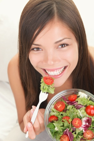 Salad. Portrait of healthy happy woman eating salad. Beautiful smiling Asian Caucasian female model.
