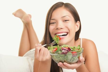 greens: Woman eating salad. Playful smiling woman eating healthy salad in bed. Beautiful cute Caucasian Asian female model.