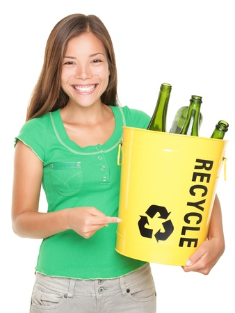 Recycle! Recycling woman pointing at recycle icon on bin with glass bottles. Caucasian / Asian girl isolated on white background. Stok Fotoğraf