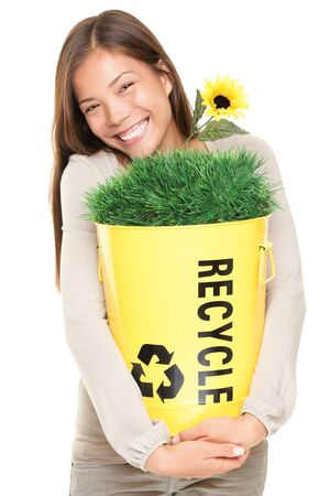 Portrait of woman showing recycle bin with grass and flower. Recycling concept. Young smiling asian  caucasian woman isolated on white background. photo