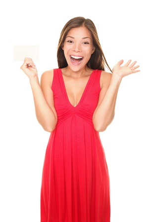holding business card: Girl in red dress showing blank sign  valentines day card. Beautiful excited smiling young woman isolated on white background (mixed race asian  caucasian). Stock Photo