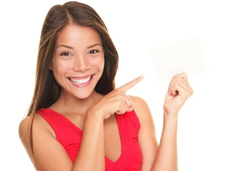 woman pointing: Girl pointing at gift card sign. Young beautiful sexy woman showing copy space on empty blank sign or gift card. Portrait of smiling Asian Chinese  white Caucasian isolated on white background.