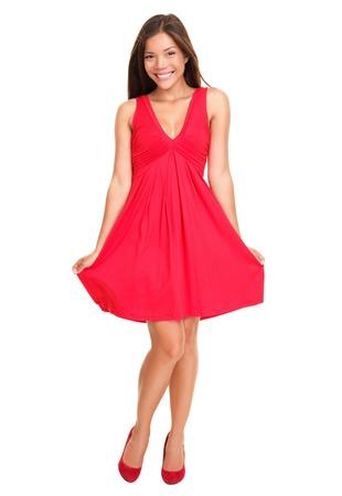 Prachtige vrouw. Portret van mooie lachende jonge vrouw staan in schattige rode jurk geïsoleerd op een witte achtergrond in volle lengte. Sexy gemengd ras Chinese Aziatisch  Kaukasische vrouwelijke model. Stockfoto