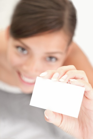 hand business card: Person showing business card. Casual woman smiling holding the card. Shallow depth of field, focus on paper with empty copy space.