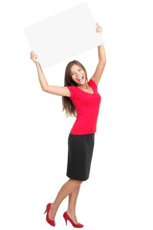 copyspace 女性の幸せな彼女の頭の上の空白記号を保持します。若くて美しい白い背景のフルの長さで分離された赤で女性を興奮させた。