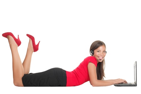 Woman with laptop computer talking in headset lying down on the floor. Isolated on full length on white background. 스톡 콘텐츠