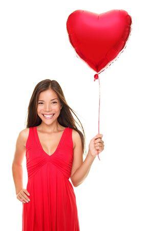Vrouw die lacht bedrijf Rode hartvormige ballon van liefde. Cute mooie jonge vrouw in liefde. Aziatisch  Kaukasische vrouwelijke model in rode jurk geïsoleerd op een witte achtergrond. Voor de dag van Valentijnskaarten concepten enz.