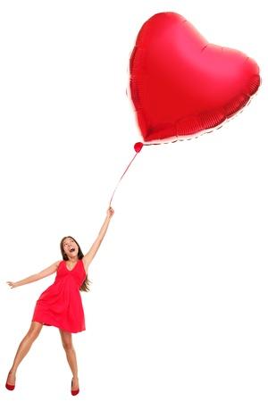 Vrouw vliegen weg met rood hart ballon. Grappige Valentijnsdag love concept beeld van mooie schattige jonge vrouw in rode jurk. Aziatisch  Kaukasische meisje geïsoleerd op een witte achtergrond in volle lengte.